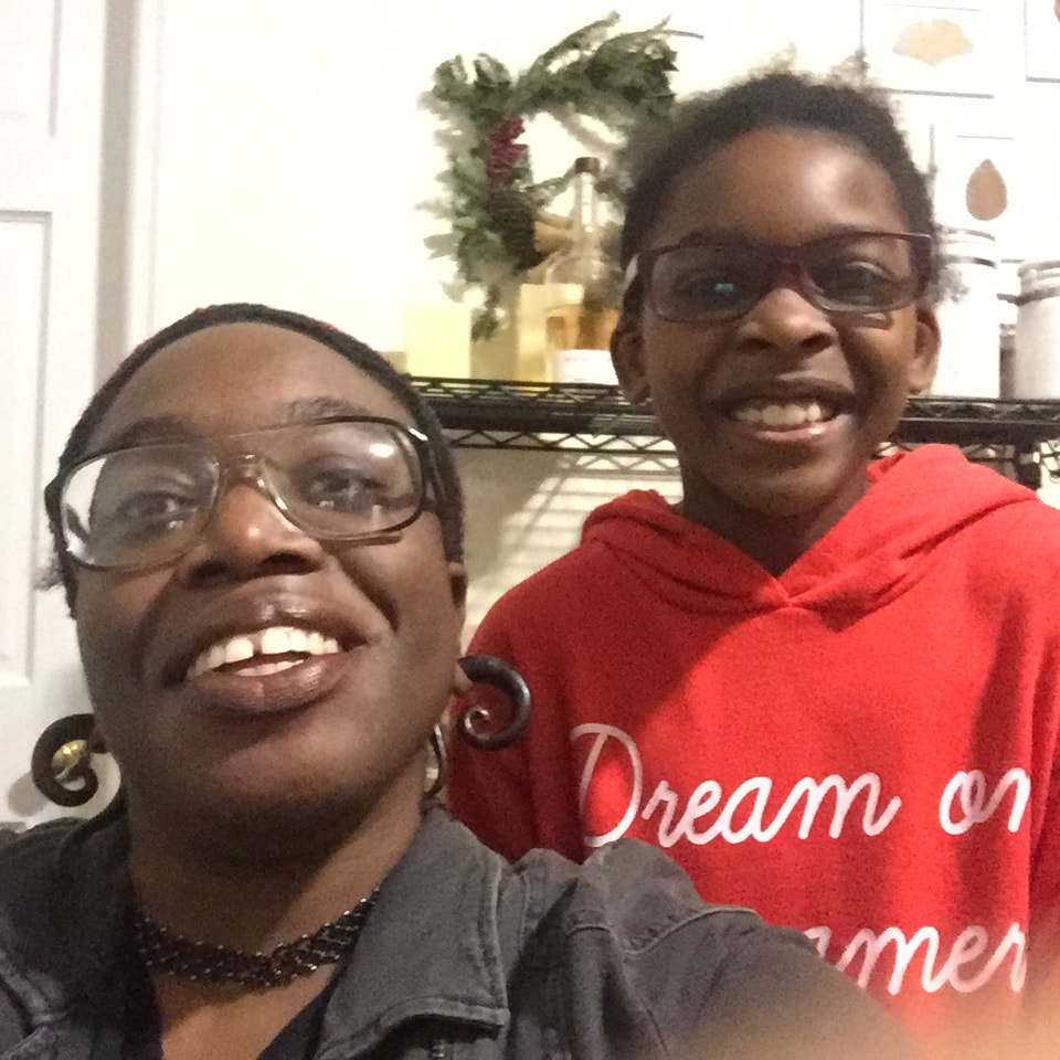 Bri M., the host of Power Not Pity poses with Amali, the guest of this episode. Bri is adorned with glasses and wooden spiral jewelry. Amali wears a red hoodie with the words