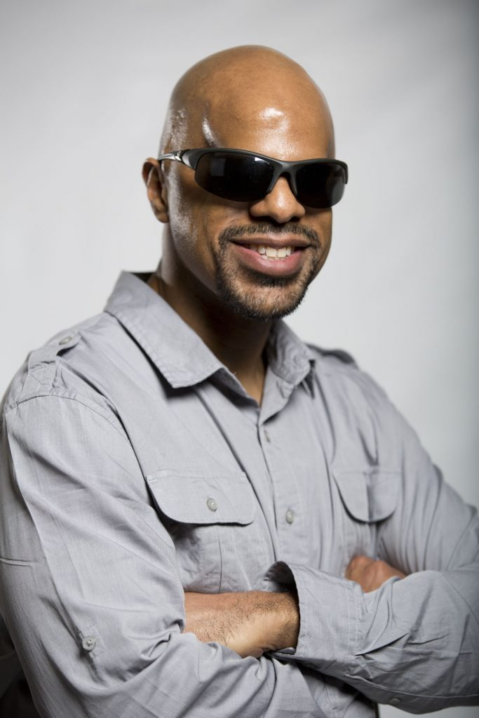A blind, bald Afro-Latino man crosses his arms and grins toward the camera. He is wearing thick black sunglasses and a grey button up shirt.